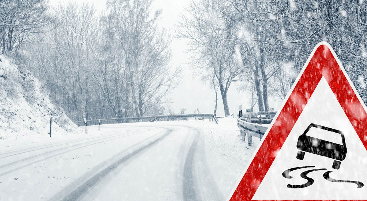 slippery winter road with warning sign or driving tip