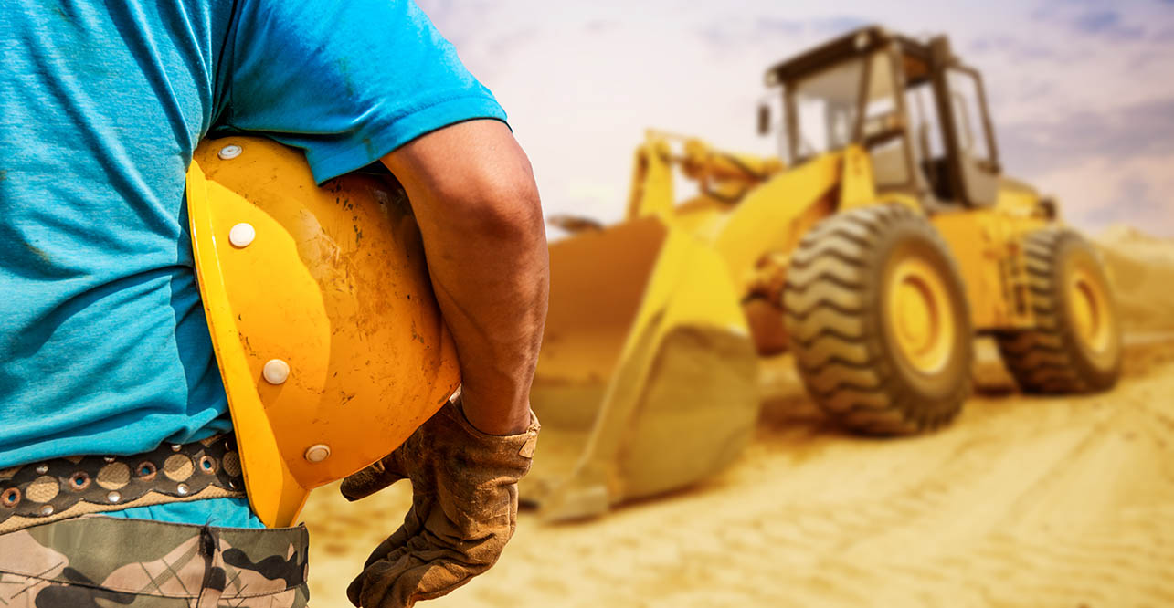 a construction worker holding a helmet, with a heavy piece of equipment in the background